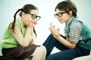 A girl and a boy wearing big black glasses are talking. [url=http://www.istockphoto.com/search/lightbox/9786682][img]http://dl.dropbox.com/u/40117171/children5.jpg[/img][/url]